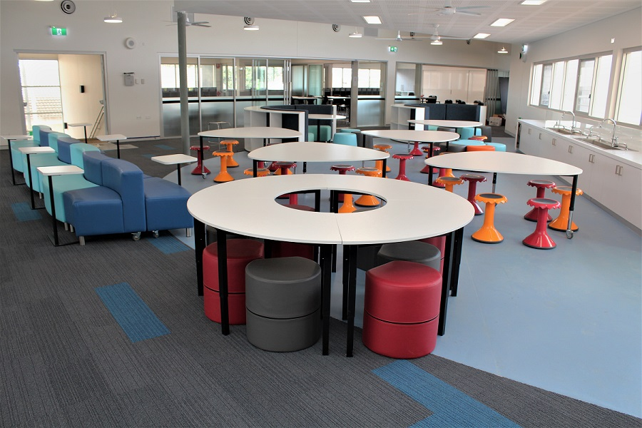 school furniture in classroom with shaped tables and seating